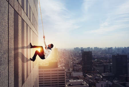Businessman climbs a building with a rope. Concept of determination 写真素材