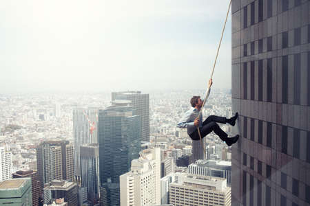 Businessman climbs a building with a rope. Concept of determination Stock fotó