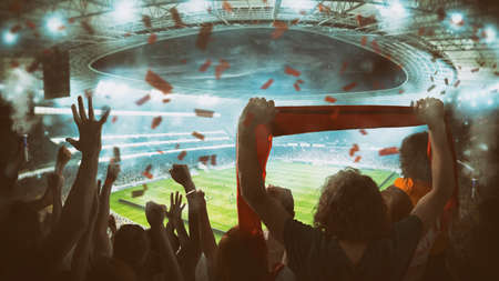 Football scene at night match with with cheering fans at the stadium Imagens