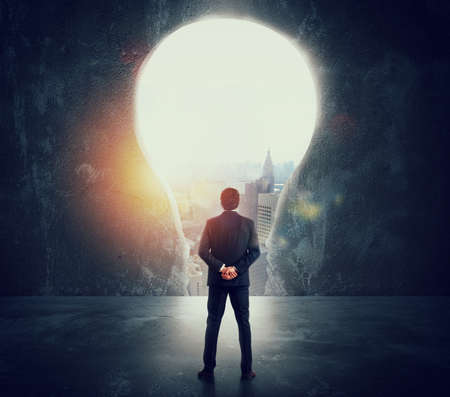 Biznesmen patrzy na dużą dziurę w ścianie w kształcie żarówki