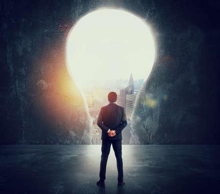 Geschäftsmann schaut auf ein großes Loch an der Wand in Form einer Glühbirne