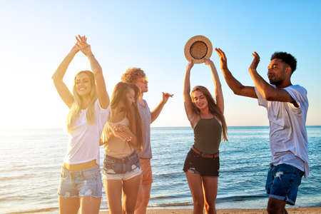 Group of friends dancing on the beach