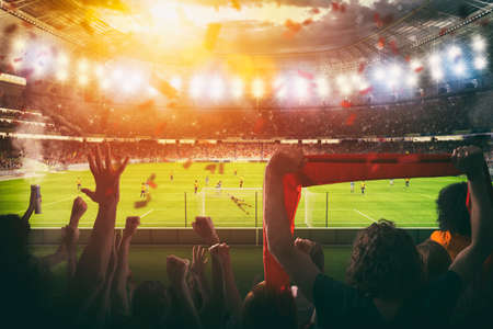 Football scene at night match with with cheering fans at the stadium Stock Photo