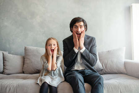 Father and daughter look both shocked something