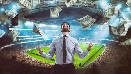 Człowiek, który raduje się na stadionie z wygrania bogatego zakładu na piłkę nożną