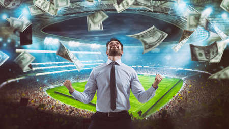 Man who rejoices at the stadium for winning a rich soccer bet Stockfoto