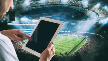 Man with tablet at the stadium to bet on the game Stock Photo