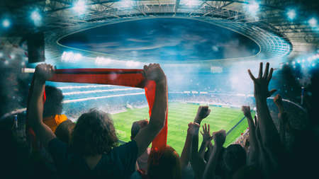 Football scene at night match with with cheering fans at the stadium Stok Fotoğraf
