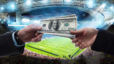 Transfer of money between two hands at the soccer stadium Standard-Bild
