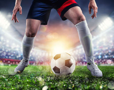 Soccer player ready to kick the soccerball at the illuminated stadium during the match
