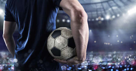 Soccer player ready to play with soccerball at the illuminated stadium during
