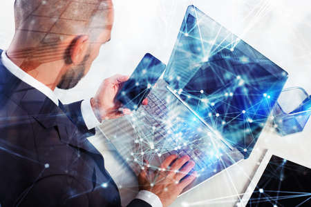 Businessman works with laptop. Concept of teamwork and partnership. double exposure with network effects 版權商用圖片