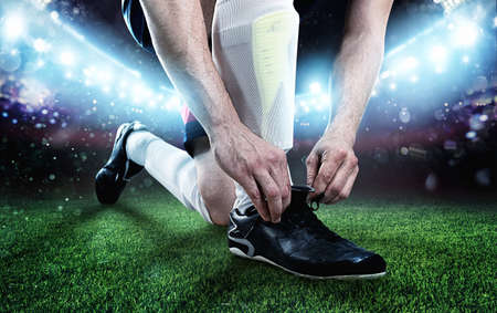 Football player adjust his shoes before the match at the stadium