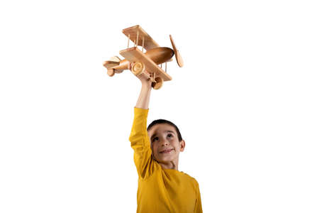 Kid plays with a wooden toy airplane. Isolated on white background 版權商用圖片