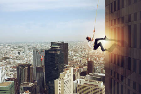 Businessman climbs a building with a rope. Concept of determination 版權商用圖片