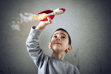 Child plays with a rocket. Concept of imagination