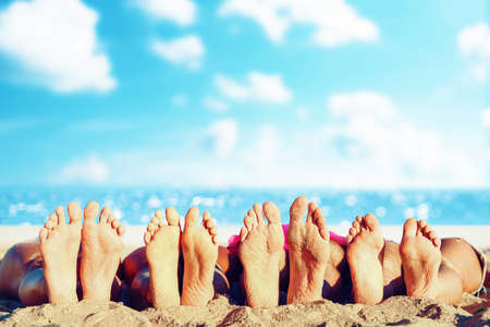 Group of friends having fun on the beach with their foots. Concept of summertime