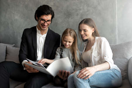 Happy little girl reads a book with her parents