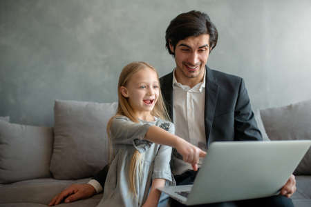 Happy little girl watching a movie on the computer with her father