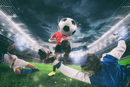 Close up of a football action scene with competing soccer players at the stadium during a night match Stock Photo - 124940662