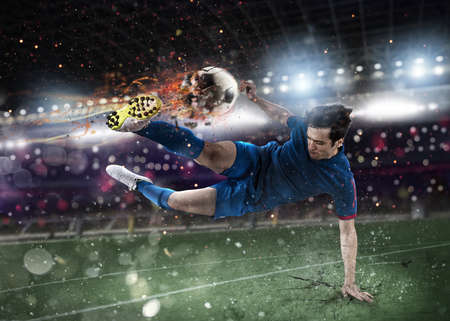 Soccer player with soccerball on fire at the stadium during the match.