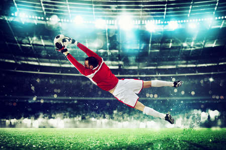 Goalkeeper catches the ball in the stadium during a football game. Stockfoto - 125018954
