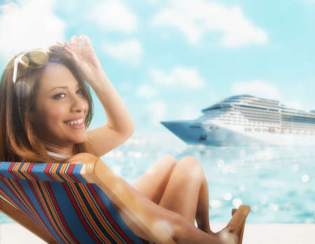 Beautiful girl sitting on a deck chair at the beach at sunset with cruiseship on background 版權商用圖片