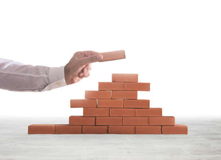 Businessman puts a brick to build a wall. Concept of new business, partnership, integration and startup Фото со стока