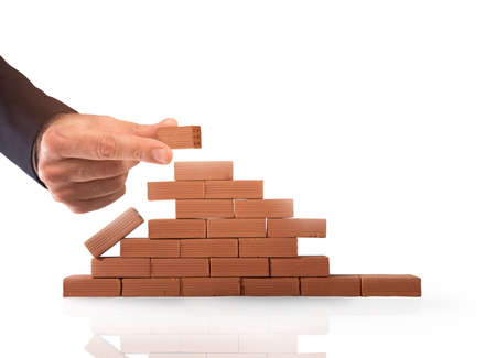 Businessman puts a brick to build a wall. Concept of new business, partnership, integration and startup Banque d'images