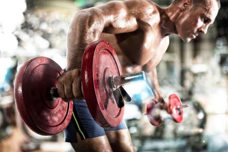 Athletic man training biceps at the gym Standard-Bild - 125188928