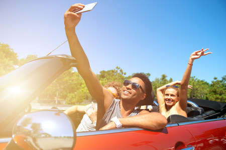 Young friends take a selfie in a cabriolet car Stockfoto