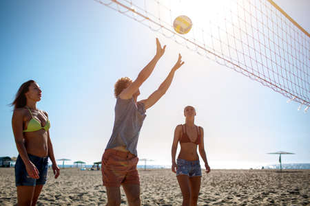 Group of friends playing at beach volley at the beach Imagens