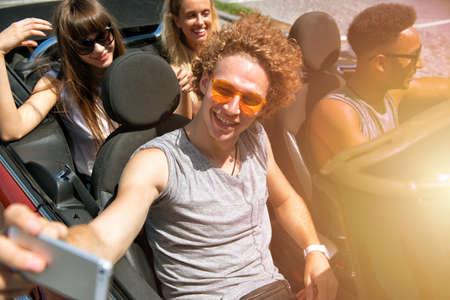 Young friends take a selfie in a cabriolet car Archivio Fotografico