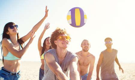 Gruppe von Freunden, die am Strand Beachvolleyball spielen
