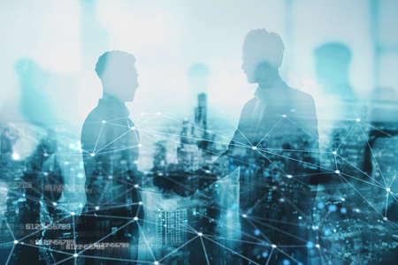 ネットワーク効果を持つオフィスでの2人のビジネスパーソンの握手。パートナーシップとチームワークの概念