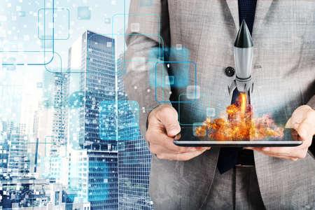 사업가는 태블릿에서 로켓을 발사합니다. 회사 시작의 개념