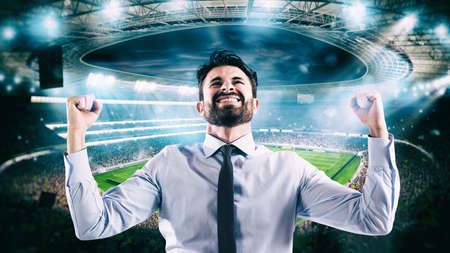 Man who rejoices at the stadium for winning a rich soccer bet Stock Photo