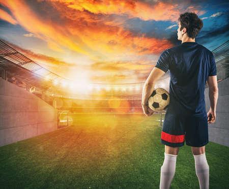 Voetballer klaar om te spelen met de bal in zijn handen bij de uitgang van de kleedkamertunnel