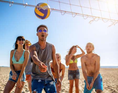 Gruppe von Freunden, die am Strand Beachvolleyball spielen Standard-Bild