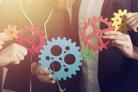 Business team connect pieces of gears. Teamwork, partnership and integration concept Archivio Fotografico