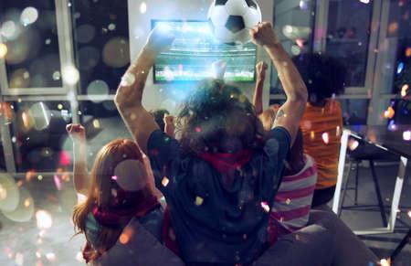 Amigos felices de los fanáticos del fútbol viendo fútbol en la televisión y celebrando la victoria con confeti cayendo. Exposición doble
