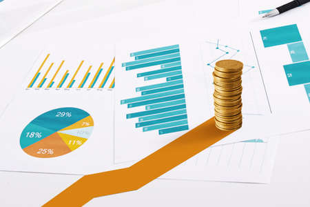 Pile of golden coin on statistical sheets. Concept of financial investment growth Stock Photo