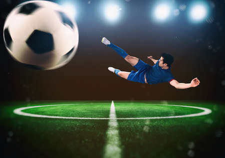 Football scene at night match with player kicking the ball with power