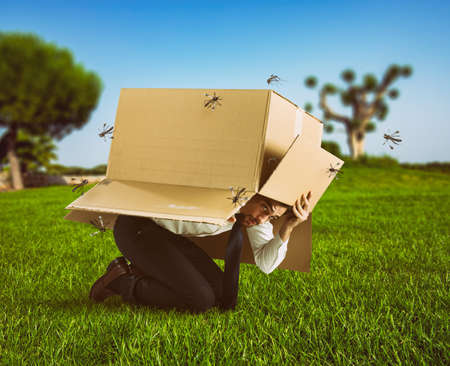 Man defends himself from the attack of mosquitoes hiding in a cardboard box Archivio Fotografico