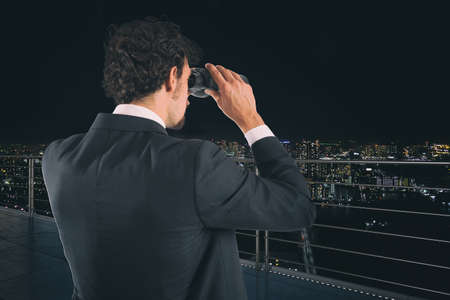 Businessman looks at the city with binoculars during night. Future and new business opportunity concept Imagens