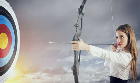 Businesswoman with bow and arrow pointing the center of the target. 写真素材