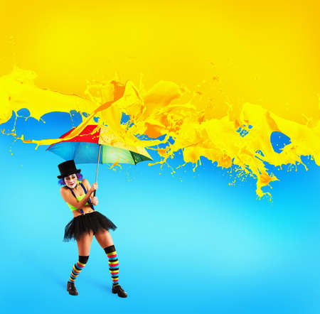Clown with umbrella covers himself from yellow color drops