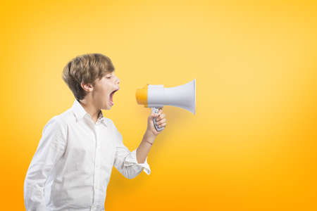 Child screaming on the megaphone on yellow background Banco de Imagens