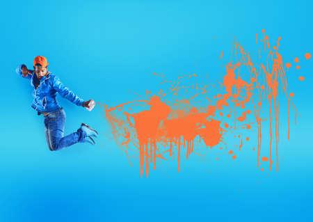 Jumping black street boy sprays orange color Stock fotó