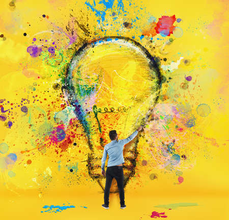 Boy draws with a brush a big light bulb. Concept of innovation and creativity. Yellow style Imagens